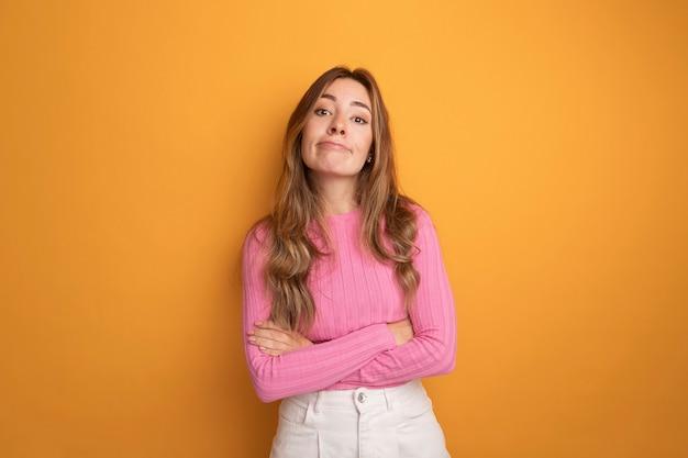 Junge schöne frau in rosa top, die mit skeptischem gesichtsausdruck in die kamera schaut, die über orange steht