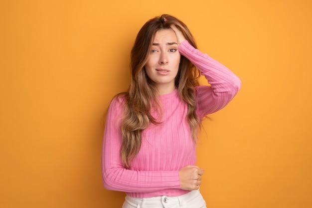 Junge schöne frau in rosa top, die verwirrt und sehr ängstlich in die kamera schaut, mit der hand auf dem kopf, die über orangefarbenem hintergrund steht