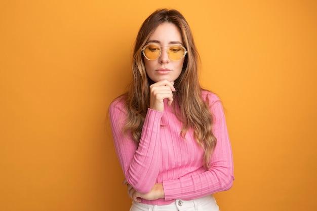 Junge schöne frau in rosa top mit brille, die mit der hand am kinn nach unten schaut, mit nachdenklichem ausdruck, der über orangefarbenen hintergrund denkt