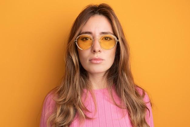 Junge schöne frau in rosa top mit brille, die mit ernstem, selbstbewusstem ausdruck in die kamera schaut