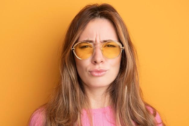 Junge schöne frau in rosa top mit brille, die stirnrunzelnd in die kamera schaut, die über orange steht