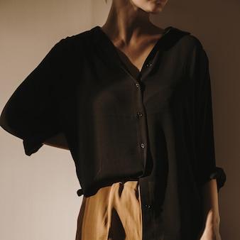 Junge schöne frau in schwarzem hemd und brauner hose, die an der wand bleibt