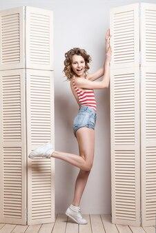 Junge schöne frau in shorts und gestreiftem top posiert vor einer jalousie
