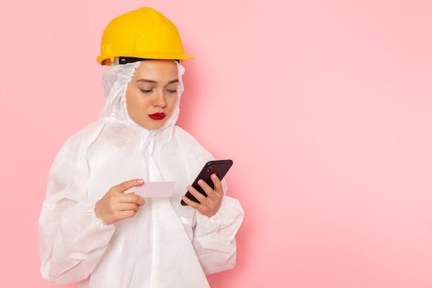 Junge schöne frau in speziellem weißen anzug und gelbem helm, der telefon auf rosa hält und benutzt