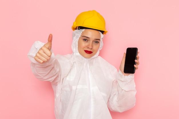 Junge schöne frau in speziellem weißen anzug und gelbem helm, der telefon mit lächeln auf rosa hält