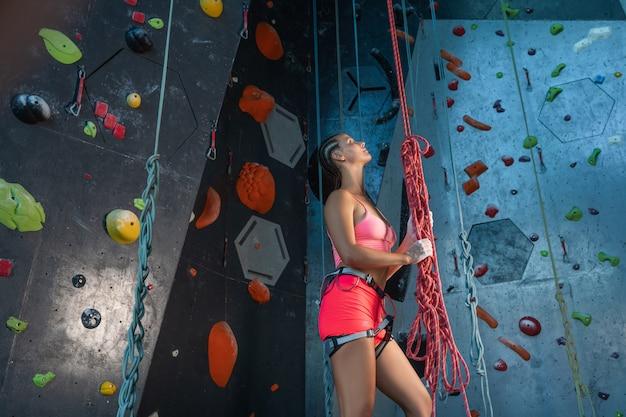 Junge schöne frau in sportbekleidung und ausrüstung für alpinismus, rote seile haltend