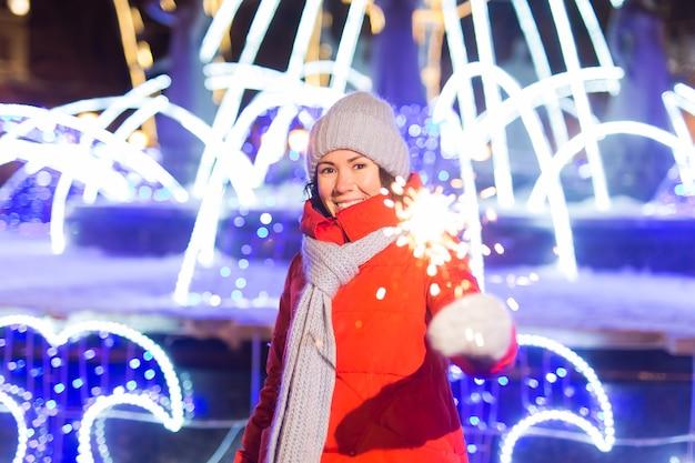 Junge schöne frau in strickmütze und schal in der stadt mit bengalischem licht, wunderkerze. konzeptfeier und weihnachten.