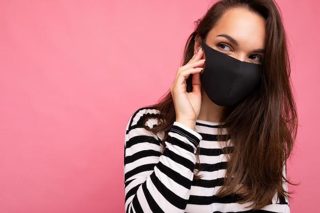 Junge schöne frau in wiederverwendbarer virusschutzmaske im gesicht gegen coronavirus einzeln auf der rosafarbenen hintergrundwand. freiraum.