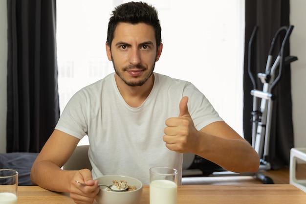 Junge schöne frau isst frühstücksflocken mit beeren und milch.