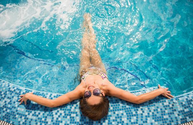 Junge schöne frau ist im swimmingpool entspannend.