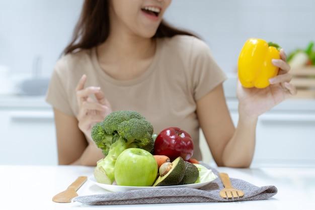 Junge schöne frau kümmern sich um ihre gesundheit, indem sie salat und frucht isst, anstatt fett und kalorien zu essen