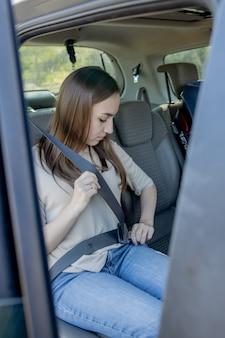 Junge, schöne frau legt einen sicherheitsgurt an und sitzt auf dem rücksitz des autos. sicherheitsfahrkonzept.