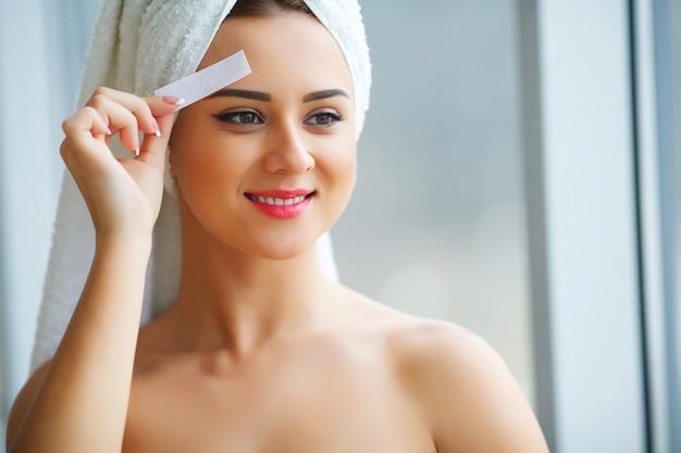 Junge schöne frau macht wachs augenlider in ihrem badezimmer.