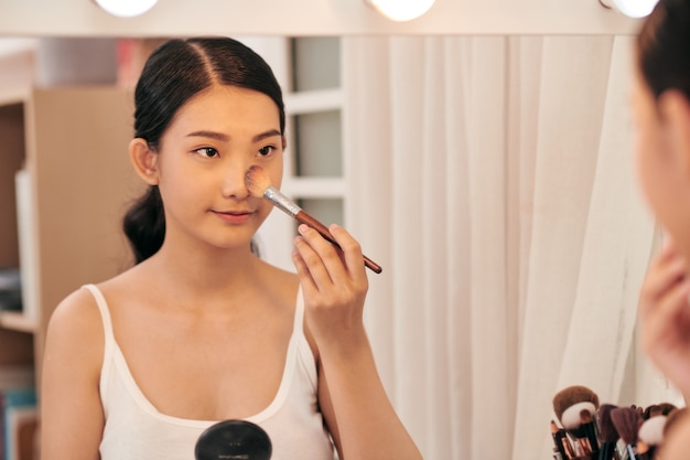 Junge schöne frau make-up in der nähe von spiegel make