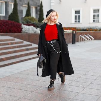 Junge schöne frau mit blondem haar mit einer lederhandtasche in einer modischen oberbekleidung des schwarzen herbstes in einer stilvollen baskenmütze geht um die stadt an einem warmen herbsttag