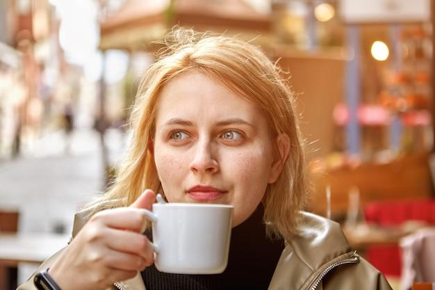 Junge schöne frau mit blonden haaren sitzt im außencafé mit kleiner tasse kaffee in ihren händen