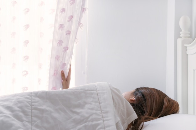 Junge schöne frau mit brünetten haaren wacht auf und öffnet morgens den vorhang auf dem bett. nahansicht.