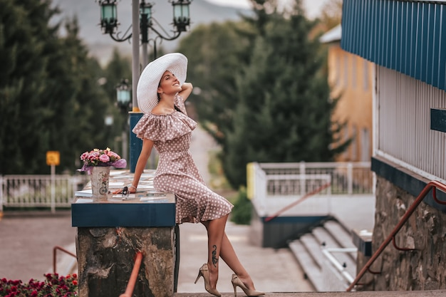 Junge schöne frau mit dem langen haar im weißen hut- und begiekleid gehend in eine stadt
