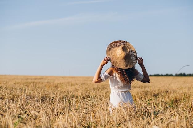 Junge schöne frau mit dem langen lockigen haar wirft in einem weizenfeld im sommer bei sonnenuntergang auf