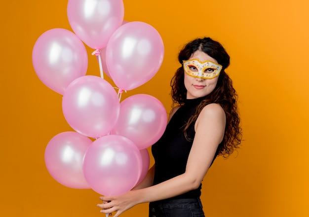 Junge schöne frau mit dem lockigen haar, das bündel luftballons in der partymaske glücklich und fröhlich geburtstagsfeierkonzept über orange hält