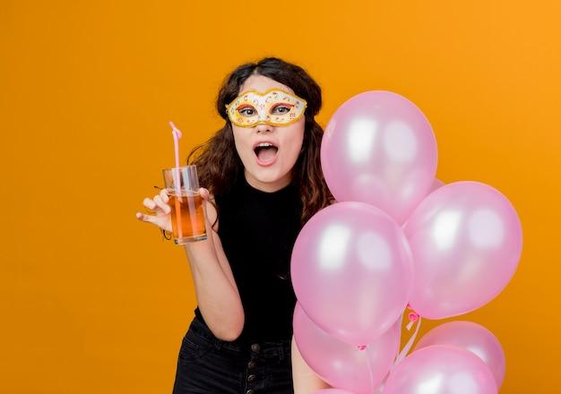 Junge schöne frau mit dem lockigen haar, das bündel luftballons und cocktail in der parteimaske glückliches und fröhliches geburtstagsfeierkonzept über orange hält