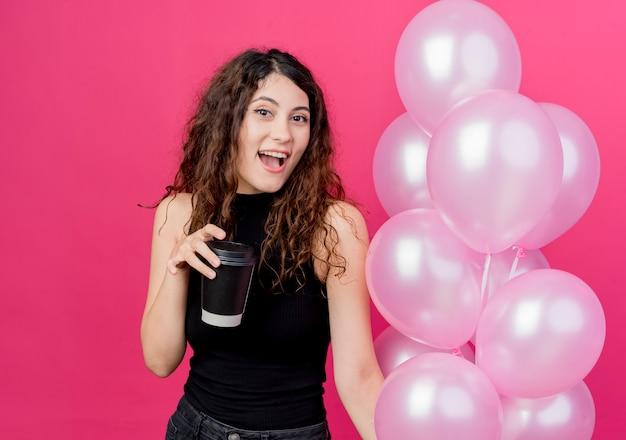 Junge schöne frau mit dem lockigen haar, das bündel luftballons und kaffeetasse hält, die fröhlich über rosa wand stehend lächelt
