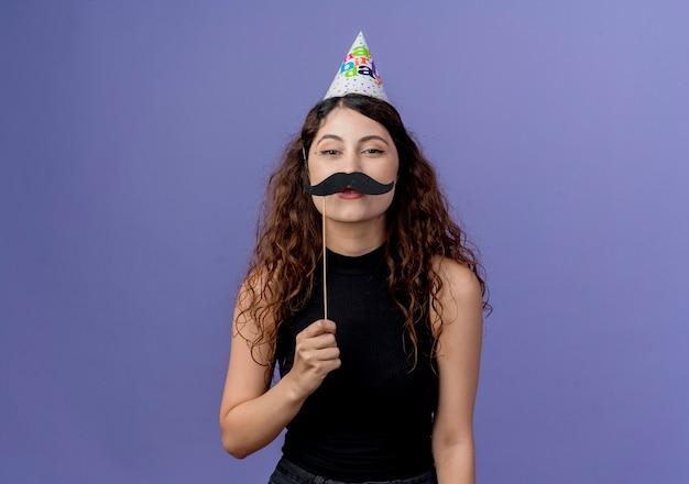 Junge schöne frau mit dem lockigen haar in der feiertagsmütze, die schnurrbart-parteistöcke hält, die über blaue wand stehen