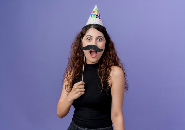 Junge schöne frau mit dem lockigen haar in der feiertagsmütze, die schnurrbart-party-sticks glücklich und überrascht hält, die über blaue wand stehen