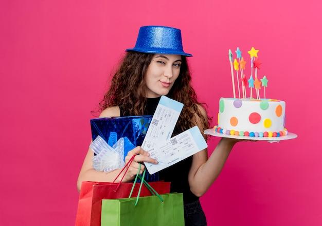 Junge schöne frau mit dem lockigen haar in einem feiertagshut, der geburtstagskuchen-geschenkbox und flugtickets lächelnd und zwinkerndes geburtstagsfeierkonzept hält über rosa wand hält