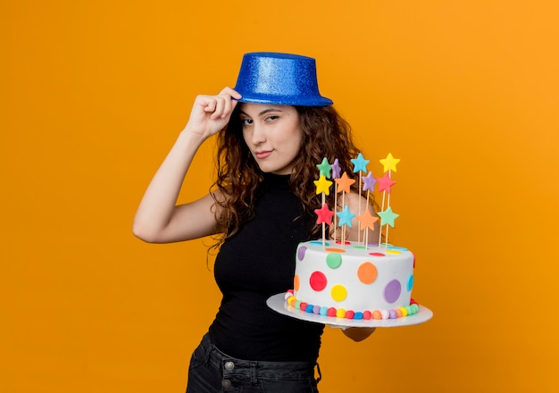 Junge schöne frau mit dem lockigen haar in einem feiertagshut, der geburtstagskuchen hält, der zuversichtlich über orange wand steht