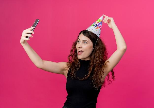 Junge schöne frau mit dem lockigen haar in einer feiertagsmütze, die das freudig lächelnde geburtstagsfeierkonzept des selfies über rosa nimmt