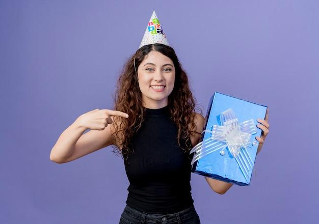 Junge schöne frau mit dem lockigen haar in einer feiertagsmütze, die geburtstagsgeschenkbox hält, die mit dem finger darauf zeigt, der fröhlich geburtstagsfeierkonzept steht, das über blaue wand steht