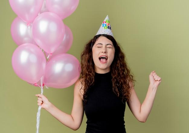 Junge schöne frau mit dem lockigen haar in einer feiertagsmütze, die luftballons hält, die faust verrückt glücklich über licht ballen