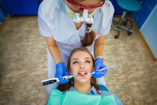 Junge schöne frau mit den schönen weißen zähnen, die auf einem zahnmedizinischen stuhl sitzen.