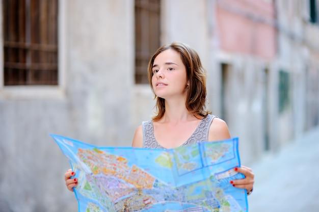 Junge schöne frau mit der papierkarte, die auf straße in venedig, italien steht