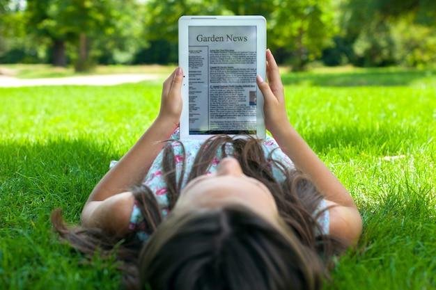 Junge schöne frau mit digitalem tablet auf grünem gras
