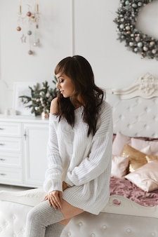 Junge schöne frau mit dunklem haar in modischen kuscheligen kleidern, die in dekoriertem weihnachtsschlafzimmer posieren.