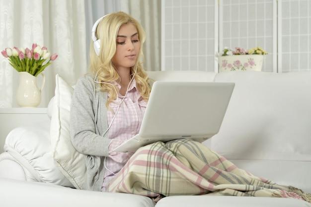 Junge schöne frau mit einem laptop-computer zu hause