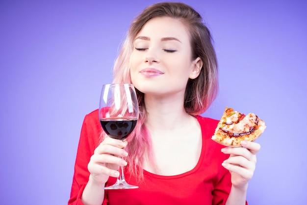 Junge schöne frau mit einem stück pizza und einem glas rotwein