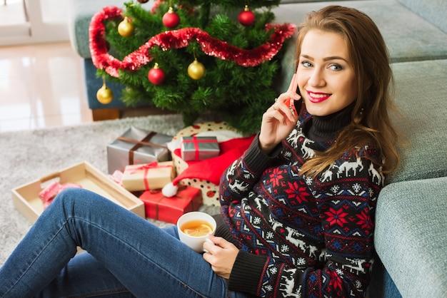Junge schöne frau mit einem telefon. weihnachtszeit