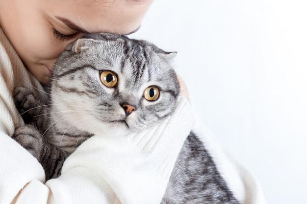 Junge schöne frau mit flauschiger katze zu hause