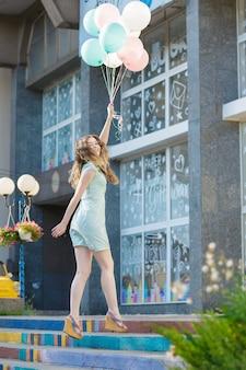 Junge schöne frau mit fliegenden bunten luftballons, die in der stadt springen