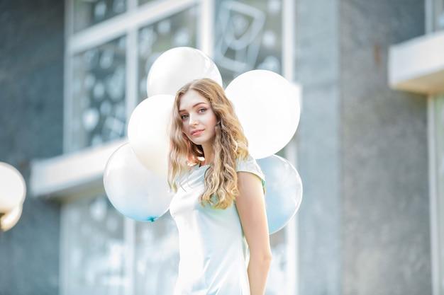 Junge schöne frau mit fliegenden bunten luftballons in der stadt