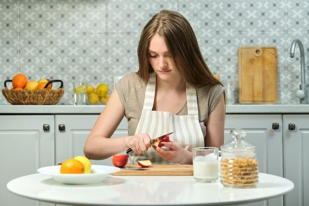 Junge schöne frau mit früchten in der küche, frau, die am tisch sitzt und äpfel schneidet