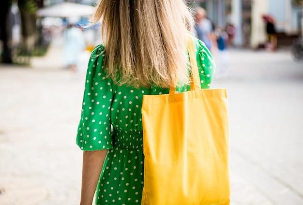 Junge schöne frau mit gelber leinen-ökotasche auf stadthintergrund