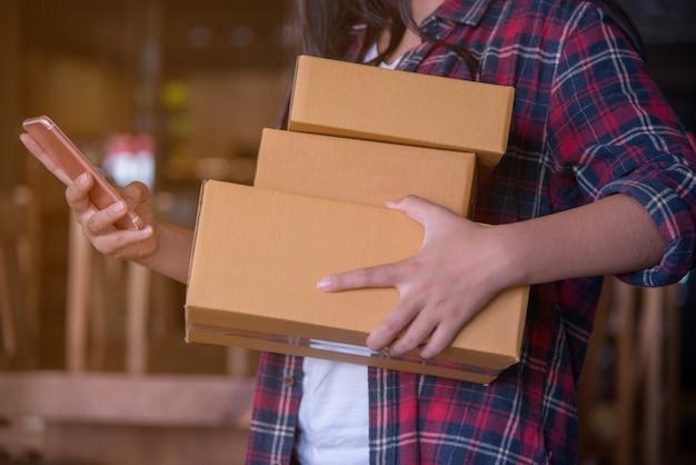 Junge schöne frau mit griffgeschenkbox in den händen