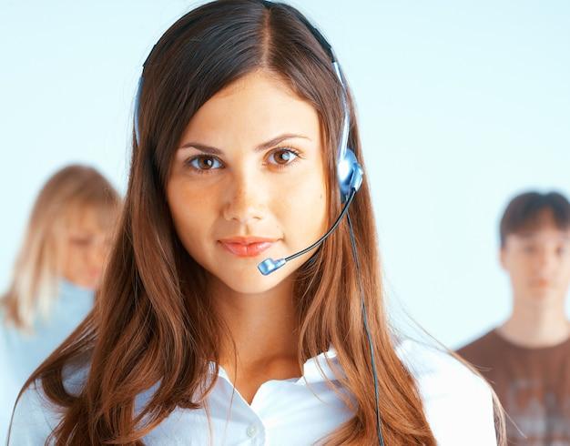 Junge schöne frau mit headset mit einigen leuten am hintergrund