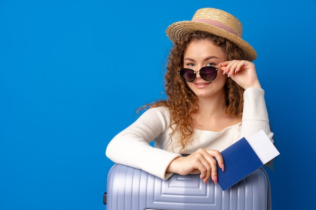 Junge schöne frau mit hut im urlaub mit koffer vor blauem hintergrund