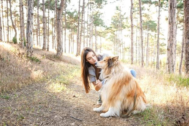 Junge schöne frau mit langen haaren, die mit colliehund gehen. draußen im park. in der nähe des meeres, sommer beatch