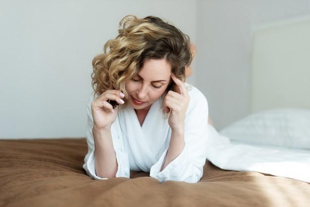 Junge schöne frau mit lockigem, fließendem haar liegt auf einem bett in einem hotelzimmer in weiß gekleidet